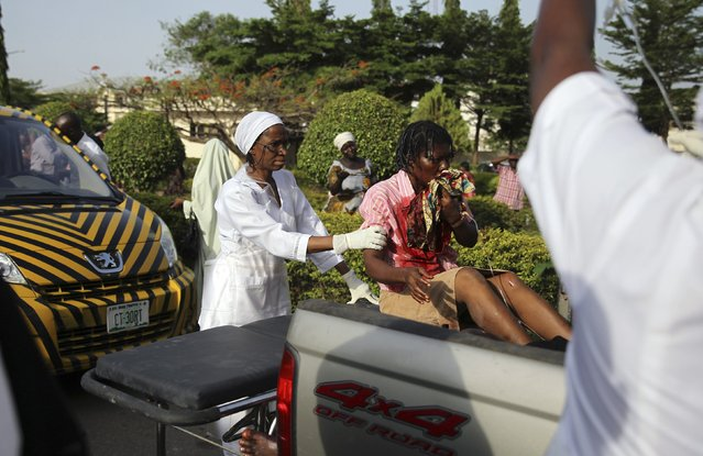 A nurse helps an injured bomb victim sitting at the back of a pickup truck at the Asokoro General Hospital in Abuja, April 14, 2014. A morning rush-hour bomb killed at least 35 people at a Nigerian bus station near the capital on Monday, raising concerns about the spread of an Islamist insurgency after the first such attack on Abuja for two years. (Photo by Afolabi Sotunde/Reuters)