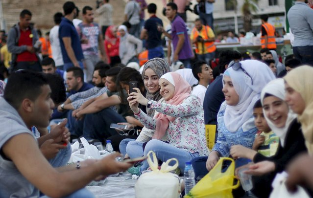 "Women take a ""selfie"" as people gather to eat their Iftar (breaking of fast) during a local initiative called ""Let's Have Iftar Together"" during the holy fasting month of Ramadan in Amman, Jordan June 27, 2015. (Photo by Muhammad Hamed/Reuters)"
