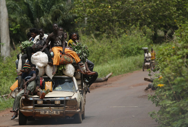 People sit on a car as they drive near Bangui April 14, 2014. (Photo by Goran Tomasevic/Reuters)