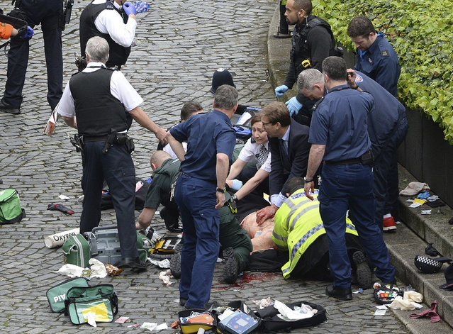 Conservative Member of Parliament Tobias Ellwood, centre, helps emergency services attend to an injured person outside the Houses of Parliament, London, Wednesday, March 22, 2017. (Photo by Stefan Rousseau/PA Wire via AP Photo)