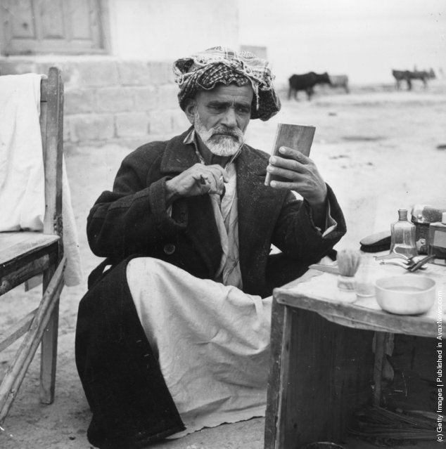 1955:  A Muslim man trims his beard at a self service barber shop at Aga Uhari, Iran