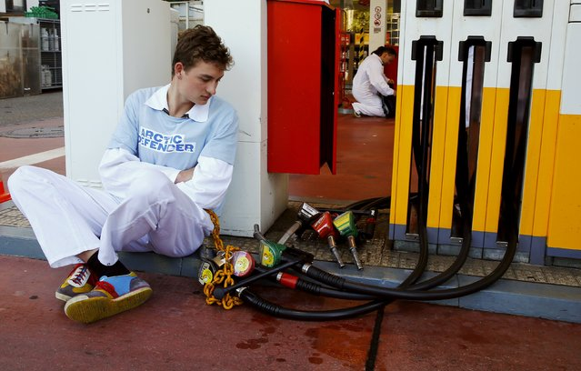 A member of Greenpeace is chained to a gas pump at a Shell gas station during a protest in Zurich June 30, 2015. Greenpeace demands to stop plans of Royal Dutch Shell to begin drilling for oil in the Arctic of Alaska. (Photo by Arnd Wiegmann/Reuters)