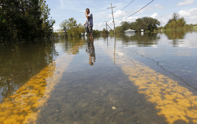 Danny Ruiz, of Violet, La., waits for a tow to pull out his brother's sunken boat trailer, after the area was flooded from Hurricane Isaac, in Braithwaite, La., Saturday, September 1, 2012. (Photo by Gerald Herbert/AP Photo)
