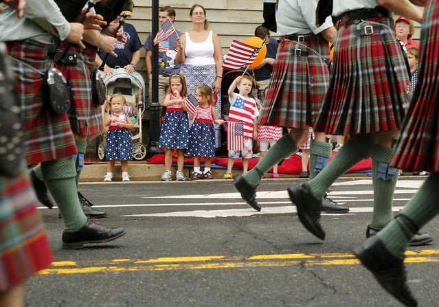 Children watch a group of bagpipers march in the Independence Day Parade in Fairfax, Virginia July 4, 2015. (Photo by Jonathan Ernst/Reuters)