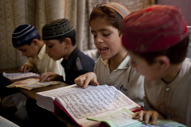 Kashmiri Muslim children recite verses from the holy Quran at a Muslim religious school, during the holy month of Ramadan in Srinagar, Indian controlled Kashmir, Thursday, July 2, 2015. Muslims across the world are observing the holy fasting month of Ramadan, where they refrain from eating, drinking and smoking from dawn to dusk. (Photo by Dar Yasin/AP Photo)