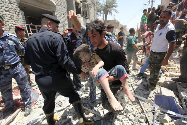 A man carries an injured child found in the rubble after an Iraqi Sukhoi jet accidentally dropped a bomb in Ni'iriya district in Baghdad July 6, 2015. The Iraqi plane accidentally dropped the bomb on an eastern Baghdad neighbourhood on Monday, police and residents said, killing at least five people and destroying several houses. (Photo by Reuters/Stringer)