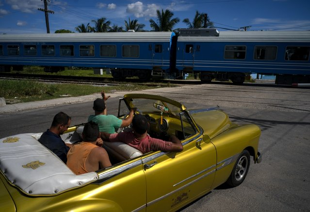 A driver in an American classic car waves as the first train using new equipment from China rides past, in Havana, Cuba, Saturday, July 13, 2019. The first train using new equipment from China pulled out of Havana Saturday, hauling passengers on the start of a 915-kilometer (516-mile) journey to the eastern end of the island as the government tries to overhaul the country's aging and decrepit rail system. (Photo by Ramon Espinosa/AP Photo)