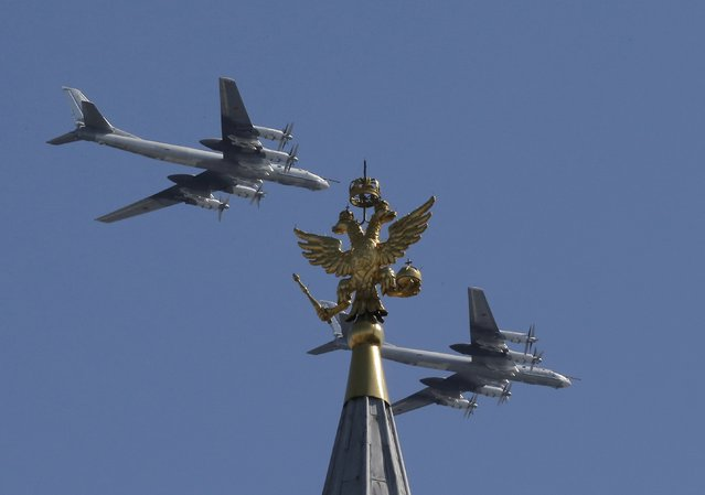 Russian Tu-95MS strategic bombers fly in formation during the Victory Day parade, marking the 71st anniversary of the victory over Nazi Germany in World War Two, above the two-headed eagle statue at the top of the State Historical Museum in Moscow, Russia, May 9, 2016. (Photo by Maxim Shemetov/Reuters)