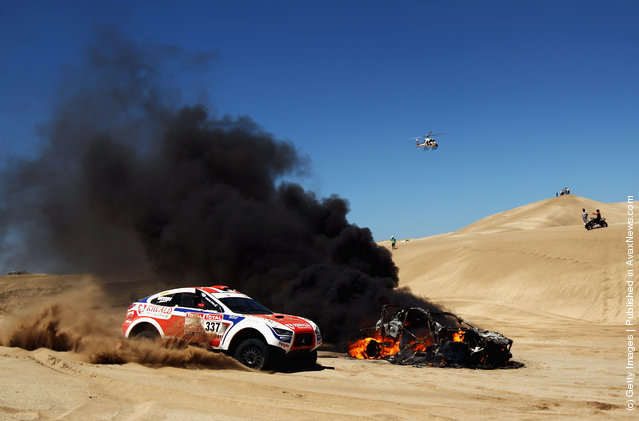 The burning car of Alfie Cox of South Africa and co-driver Jurgen Schroder sits in the sand dunes during stage one of the 2012 Dakar Rally