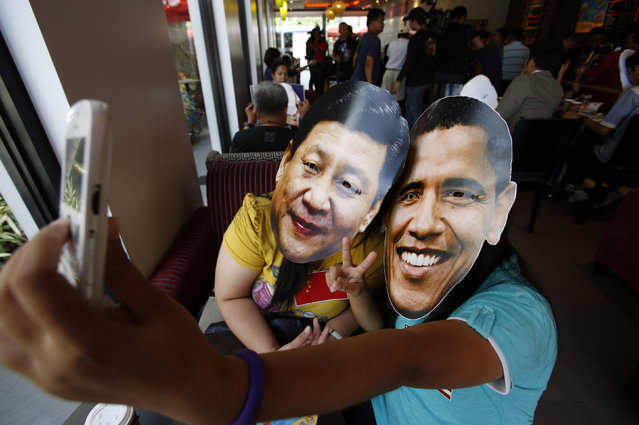 "Members of activist Party List group ""Akbayan"" wearing picture cut-out masks of U.S. President Barack Obama and China's President Xi Jinping make a ""selfie"" with a mobile phone in a coffee shop in Quezon city, Metro Manila April 27, 2014. Members of Akbayan Youth sat down inside a coffee shop wearing Xi and Obama masks while sipping coffee with each other as a creative symbolization of the two superpower's struggle for power in the Asia-Pacific region, a day ahead of a scheduled state visit by Obama. (Photo by Erik De Castro/Reuters)"