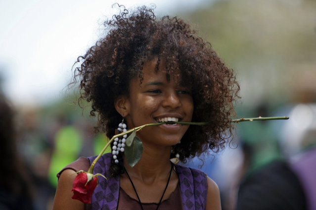A student carries a flower in her mouth during a protest against a tuition increase outside the University of Puerto Rico in San Juan, Puerto Rico, Wednesday, April 23, 2014. The 24-hour protest was called even though officials at the university have extended a one year moratorium on the four percent increase. (Photo by Ricardo Arduengo/AP Photo)