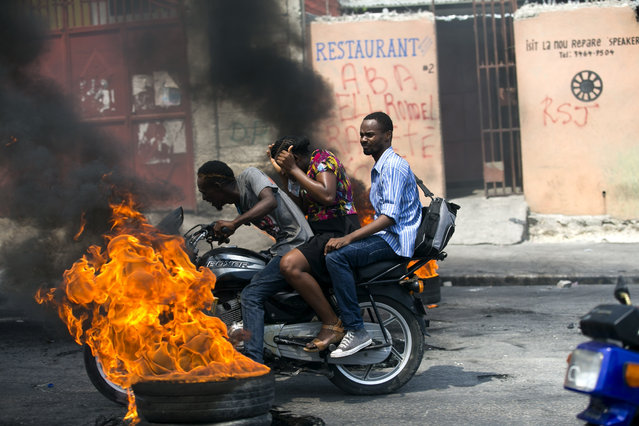 A moto-taxi driver takes two passengers past a burning barricade set up by people protesting fuel shortages in Port-au-Prince, Haiti, Monday, September 16, 2019. Haiti was at a standstill Monday with no public transportation available and closed banks, government offices, and schools amid street protests due to a fuel crisis. (Photo by Dieu Nalio Chery/AP Photo)