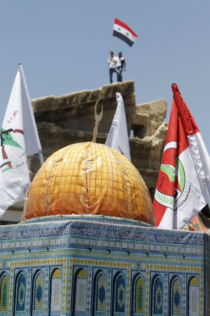 A man waves the Syrian national flag, as Palestinians living in Syria hold a replica of the Dome of the Rock and Palestinians faction flags during a rally marking the annual al-Quds Day, or Jerusalem Day, on the last Friday of the Muslim holy month of Ramadan in Damascus, Syria July 10, 2015. (Photo by Omar Sanadiki/Reuters)