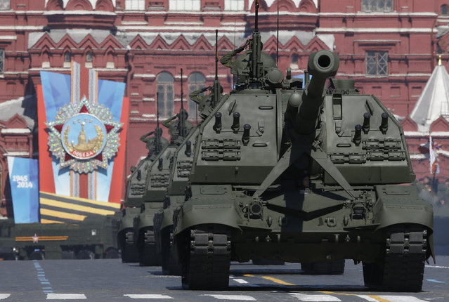 Russian servicemen onboard self-propelled artillery vehicles salute during the Victory Day Parade in Moscow's Red Square May 9, 2014. (Photo by Sergei Karpukhin/Reuters)