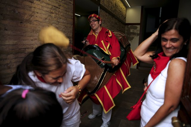 """Women react as they are hit with a sponge by a """"Zaldiko"""" (men wearing horse figures) during San Fermin festival's """"Comparsa de gigantes y cabezudos"""" (Parade of Giants and Big Heads) in Pamplona, northern Spain, July 13, 2015. (Photo by Susana Vera/Reuters)"""