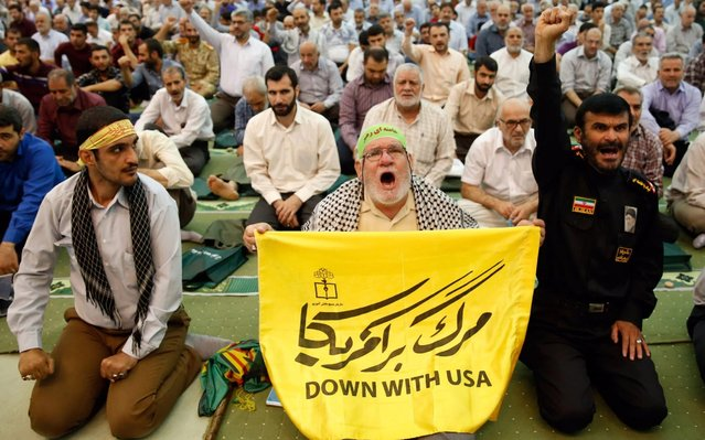An Iranian man holds an anti-US placard and shouts slogans during Friday prayers at the Imam Khomeini Mosque in Tehran, Iran, 19 July 2019. According to media reports, Iran has denied that the USS Boxer shot down an Iranian drone after it came within a kilometer of the ship in the Strait of Hormuz. (Photo by Abedin Taherkenareh/EPA/EFE/Rex Features/Shutterstock)