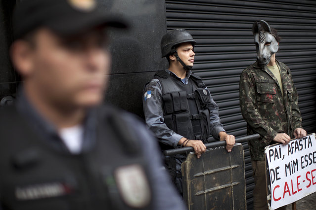 An activist wearing a donkey mask stands next to police as they stand guard outside a military club during a protest in downtown Rio de Janeiro, Brazil, Thursday March 29, 2012. A club of retired military officers held its annual celebration of Brazil's 1964 military coup as usual, but faced protestors as members arrived for the event. (Photo by Felipe Dana/AP Photo)