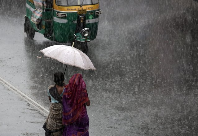 Indian commuters wade through heavy rain on street in Calcutta, eastern India, 23 May 2016. A monsoon shower hit the city and disrupted daily life. The Indian monsoon season usually takes place between May and September. (Photo by Piyal Adhikary/EPA)