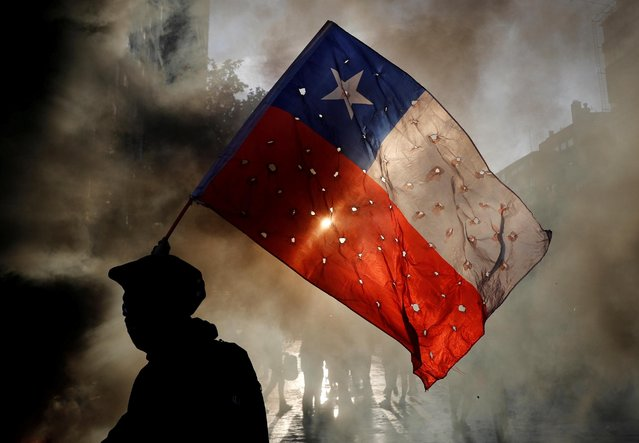 A demonstrator waves a Chile flag riddled with holes during a protest against Chile's government in Santiago, Chile on October 31, 2019. (Photo by Henry Romero/Reuters)