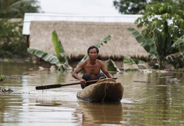 A man padles a canoe along a flooded street at a village in Kawlin township, Sagaing division, Myanmar, July 21, 2015. (Photo by Soe Zeya Tun/Reuters)