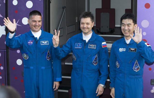 Kjell Lindgren of the U.S., Oleg Kononenko of Russia and Kimiya Yui of Japan, a member of the International Space Station (ISS) crew, waves near a bus before departure for a final pre-launch preparation at the Baikonur cosmodrome, Kazakhstan, July 22, 2015. (Photo by Shamil Zhumatov/Reuters)