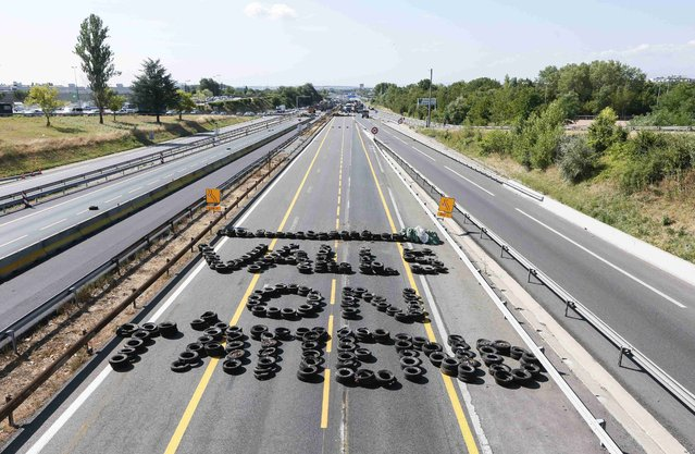 """The slogan """"Valls, we're waiting for you"""", in reference to France's prime minister, is written with tyres on A6 highway as French farmers block it access in Limonest, near Lyon, France, to protest against a squeeze in margins by retailers and food processors July 23, 2015. France announced measures worth up to 1.1 billion euros ($1.2 billion) on Wednesday to support its livestock farmers and try to halt protests which have escalated in recent days into road blockades in the northwest. (Photo by Robert Pratta/Reuters)"""