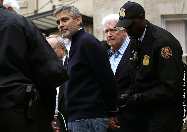 Actor George Clooney (L) is arrested with his father Nick Clooney (2R) during a demonstration outside the Embassy of Sudan March 16, 2012 in Washington