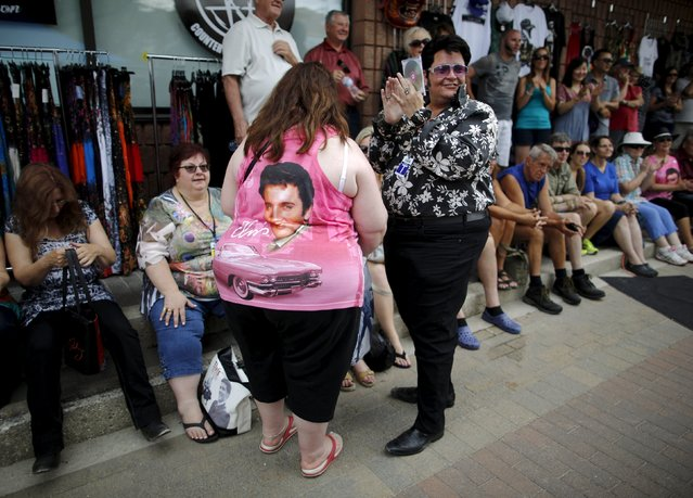 Elvis Presley tribute artist Marcus Wells (R) of Toronto speaks with a woman wearing a souvenir shirt at the four-day Collingwood Elvis Festival in Collingwood, Ontario July 25, 2015. (Photo by Chris Helgren/Reuters)