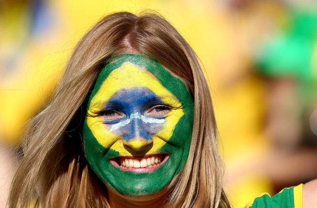 "A Brazil fan with painted face soaks up the atmosphere inside the Itaquerao stadium ahead of kick off in the opening match of the 2014 World Cup vs Croatia 2014 FIFA World Cup, Group A, Brazil v Croatia, Arena Corinthians, S""o Paulo, Brazil, on June 12, 2014. (Photo by Kieran  McManus/BPI/Rex Features)"