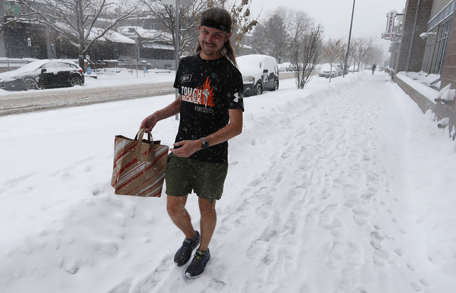 Ryan Lusk, a native of Duluth, Miin., who nows lives in Denver, heads out of a grocery store with his purchases as a storm packing snow and high winds sweeps in over the region Tuesday, November 26, 2019, in Denver. Stores, schools and government offices were closed or curtailed their hours while on another front, Thanksgiving Day travellers were forced to wrestle with snow-packed roads and flight delays or cancellations throughout the intermountain West. (Photo by David Zalubowski/AP Photo)