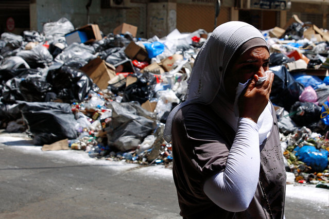 A Lebanese woman covers her nose from the smell as she walks on a street partly blocked by piles of garbage in Beirut, Lebanon, Monday, July 27, 2015. Protesters have closed the highway linking Beirut with southern Lebanon over the country's trash crisis. (Photo by Hassan Ammar/AP Photo)