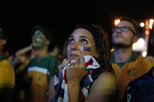 An Australian soccer fan embraces a flag as she watches the 2014 World Cup soccer match between Chile and Australia which was broadcast on a large screen at Copacabana beach in Rio de Janeiro June 13, 2014. (Photo by Pilar Olivares/Reuters)