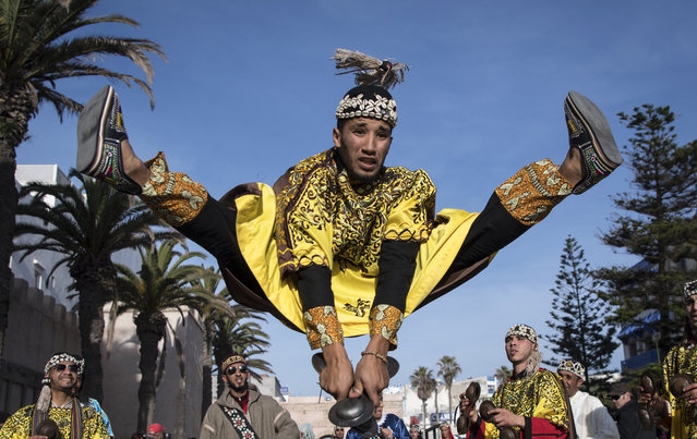 "A Gnawa traditional group performs in the city of Essaouira on December 14, 2019, to celebrate the decision of adding the Gnawa culture to UNESCO's list of Intangible Cultural Heritage of Humanity. Gnawa culture, a centuries-old Moroccan practice rooted in music, African rituals and Sufi traditions, was added to UNESCO's list of Intangible Cultural Heritage of Humanity earlier in the week. Gnawa refers to a ""set of musical productions, fraternal practices and therapeutic rituals where the secular mixes with the sacred"", according to the nomination submitted by Morocco. Often dressed in colourful outfits, Gnawa musicians play the guenbri, a type of lute with three strings, accompanied by steel castanets called krakebs. (Photo by Fadel Senna/AFP Photo)"