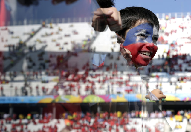 A young Chilean fan looks out onto the pitch before the group B World Cup soccer match between the Netherlands and Chile at the Itaquerao Stadium in Sao Paulo, Brazil, Monday, June 23, 2014. (Photo by Felipe Dana/AP Photo)