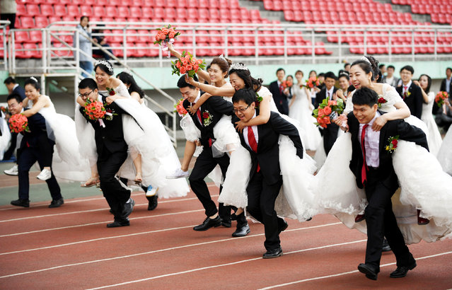 Couples take part in a competition during a mass wedding of 64 doctoral student couples at Harbin Institute of Technology, a university in Harbin, Heilongjiang province, China, June 4, 2017. (Photo by Reuters/Stringer)