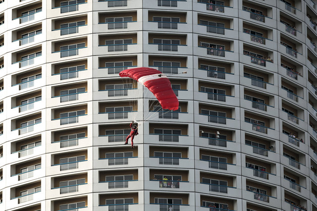 "A parachutist, dubbed the ""Red Lions"", descends past the Swissotel during the National Day Parade preview in Singapore, August 1, 2015. Singapore is commemorating its golden jubilee with a year-long national campaign titled ""SG50"" in celebration of its 50th anniversary of independence from Malaysia on 09 August 2015. (Photo by Wallace Woon/EPA)"