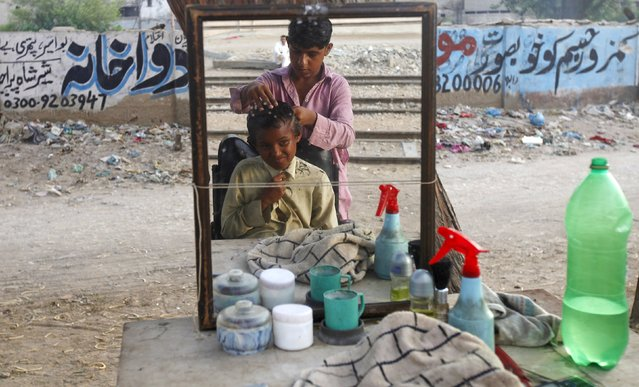 A boy has his head shaved at a makeshift barber's stall along a street in Karachi, Pakistan, July 21, 2015. (Photo by Athar Hussain/Reuters)