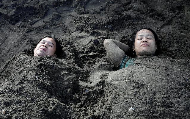 Residents are pictured with their bodies covered in sand at the beach as they celebrate Easter Sunday in Tanza, Philippines, April 16, 2017. (Photo by Erik De Castro/Reuters)