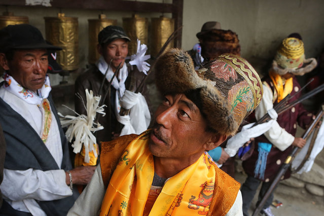 Traditionally dressed representatives of Upper Mustang's villages gather before firing antique guns to chase demons from the city during the Tenchi Festival on May 27, 2014 in Lo Manthang, Nepal. The Tenchi Festival takes place annually in Lo Manthang, the capital of Upper Mustang and the former Tibetan Kingdom of Lo. Each spring, monks perform ceremonies, rites, and dances during the Tenchi Festival to dispel evils and demons from the former kingdom. (Photo by Taylor Weidman/Getty Images)