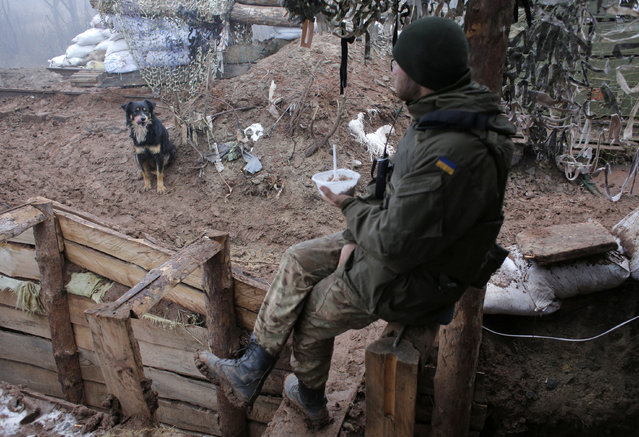 A Ukrainian soldier eats in a trench in the front line near the town of Novoluhanske in the Donetsk region, Ukraine, Monday, December 9, 2019. A long-awaited summit in Paris on Monday aims to find a way to end the war in eastern Ukraine, a conflict that after five years and 14,000 lives lost has emboldened the Kremlin and reshaped European geopolitics. (Photo by Vitali Komar/AP Photo)