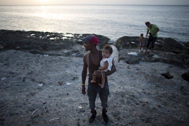 School worker Ivan Gago, 33, holds his 5 months old son as he watches the sunset in Havana, August 5, 2015. (Photo by Alexandre Meneghini/Reuters)
