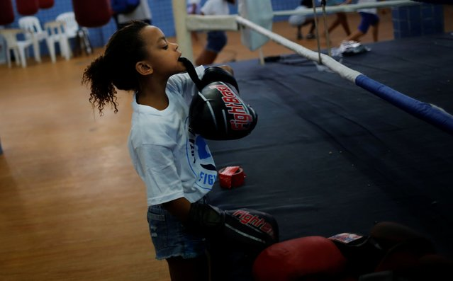 A girl puts on boxing gloves during an exercise session at a boxing school, in the Mare favela of Rio de Janeiro. (Photo by Nacho Doce/Reuters)
