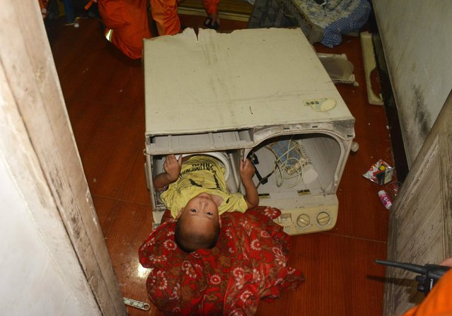 A 3-year-old boy is seen stuck in the cylinder of a washing machine as firefighters carry out rescue operations in Yongjia county of Wenzhou, Zhejiang province July 10, 2014. The firefighters successfully rescued the boy, who got stuck while playing inside the washing machine, by tearing apart the machine and cutting the cylinder open, local media reported. The boy did not sustain any injuries, the report added. (Photo by Reuters/Stringer)
