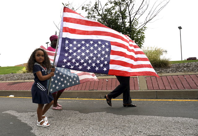 A girl carries an upside down U.S. flag during a protest march in Ferguson, Missouri August 8, 2015. (Photo by Rick Wilking/Reuters)