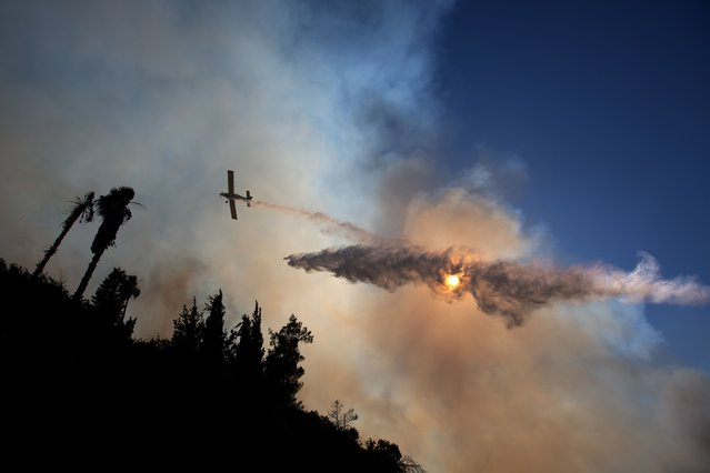 A plane drops water over Jerusalem forest in an attempt to control wildfires on June 25, 2014 near the Jerusalem neighborhood of Ein Kerem. (Photo by Menahem Kahana/AFP Photo)