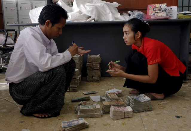 Workers count kyat banknotes at the office of a local bank in Yangon in this April 2, 2012 file photo. Citigroup Inc and Standard Chartered Plc are set to advise Myanmar on its first credit rating, according to people with direct knowledge of the matter, paving the way for the country to issue its maiden international bond. (Photo by Soe Zeya Tun/Reuters)