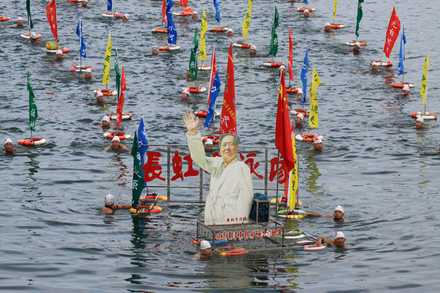 People swim with a portrait of late Chinese Chairman Mao Zedong in Han River, a large branch of the Yangtze River, as hundreds of people take part in celebration of the upcoming 51st anniversary of Chairman Mao swimming in the Yangtze River on July 16, 1966 in Xiangyang, Hubei province, China, July 15, 2017. (Photo by Reuters/China Stringer Network)