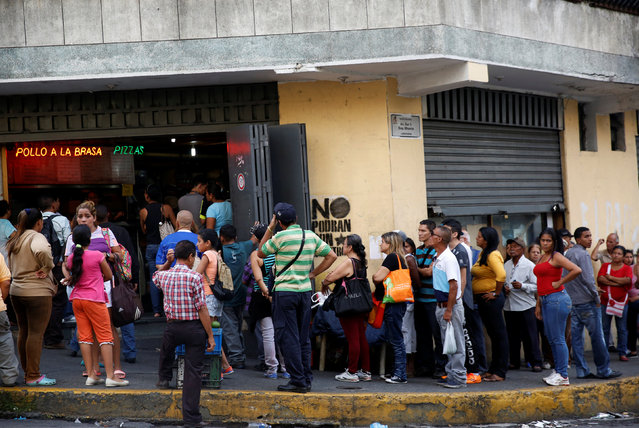 People line up as they gather to try to buy food outside a store in Caracas, Venezuela, June 23, 2016. (Photo by Mariana Bazo/Reuters)