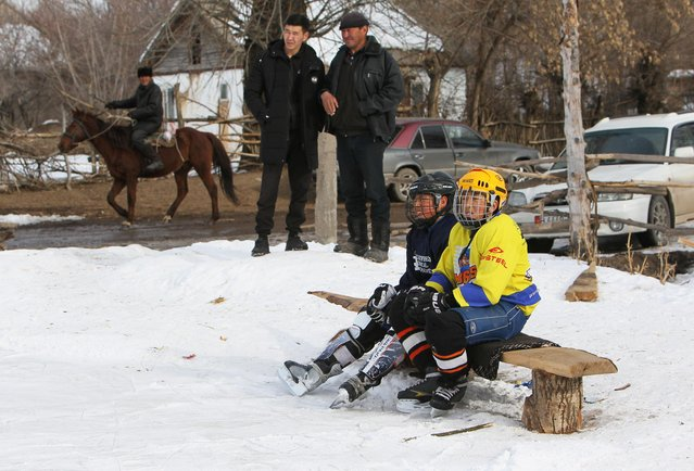 Young hockey players and local residents watch a training match between Kyrgyzstan's first female hockey team and the male team of the Karakol lyceum, in the village of Otradnoye, Kyrgyzstan on February 4, 2020. (Photo by Vladimir Pirogov/Reuters)