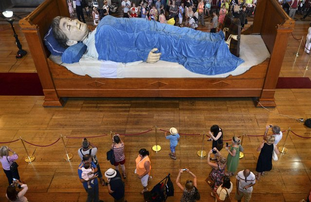 A giant puppet of a grandmother lies on a bed inside St. George's Hall in Liverpool, England, on Jule 23, 2014. The grandmother is one of two giant models made for a World War I commemorative event. (Photo by Nigel Roddis/Reuters)